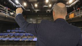 Man speaking and moving clenched fist up front public in hall back view. Man raising hand with fist on business meeting in conference hall stock footage