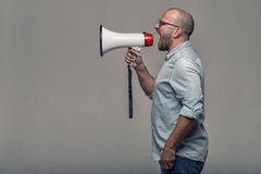Man speaking over a megaphone. As he makes a public address, participates in a protest or organises a rally or promotion, over grey with copy space to the side Stock Photos