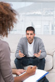 Man speaking to a therapist. While she is taking notes Royalty Free Stock Images