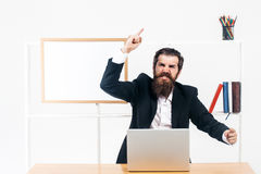 Man speaks emotionally. Bearded man in black suit speaks emotionally gesticulating by hands at desk with laptop in office Stock Photo
