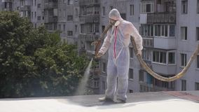 A man in a special form on the roof uses a chemical solution, painting the roof, insulates the roof stock footage