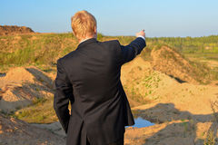 The man specifies in a distance. The man against a sandpit specifies by a hand in a distance in a jacket Stock Photography