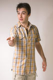 The man specifying a finger. On a grey background Stock Photos