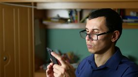 Man spectacled glasses typing a message on the phone smartphone social media stock video footage