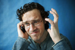 The man in spectacles. Emotional talking on a cell phone stock photo