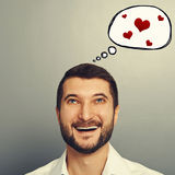 Man with speech bubble and red hearts. Portrait of happy laughing man with speech bubble and red hearts over grey background stock images