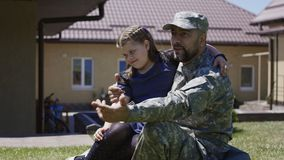 Man spending time with children before army. Adult man in uniform of serviceman embracing daughter and relaxing with son in summer garden before leaving to army stock video