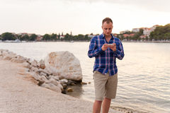 Man spending time on seashore and using phone. Royalty Free Stock Images