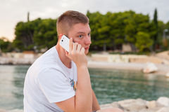 Man spending time on seashore and using phone. Stock Photography