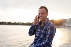 Man spending time on seashore and using phone. Stock Images