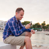 Man spending time on seashore and using phone. Royalty Free Stock Photos