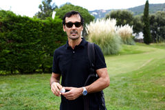 A man spends his holiday in the park. Portrait of handsome rich man in glasses having good leisure time during golf game, golfer holding ball in the hands stock images