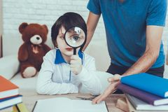 Father is Doing a Homework with Son. Man Spends Time with His Son. Father is Engaged in Raising Child. Father Pointing on Homework to Son. Boy is Looking Through royalty free stock photography