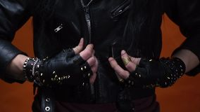 A man with spiked leather gloves puts on and zips up his leather jacket, close up. Young man in rocker clothes zipping up his leather jacket, and fastens his stock video footage