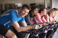 Man in a spinning class at a gym turning to smile at camera Stock Images