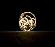 Man is spinning the poi with fire Stock Image