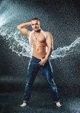Man with a splash. Attractive young man with wet clothes under the rain and splash of water, studio photoshoot Royalty Free Stock Photography