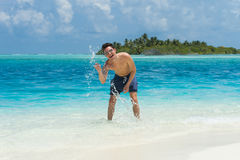 Man splash water of the ocean at the background of island Royalty Free Stock Photography
