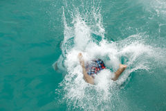 Man splashing in blue sea Stock Images