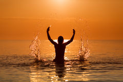 Man Splashing Water with his hands on a sea in a sunrise.  Stock Photos
