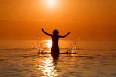 Man Splashing Water with his hands on a sea in a sunrise.  Royalty Free Stock Photo