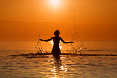 Man Splashing Water with his hands on a sea in a sunrise.  Stock Photography