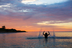 Man Splashing Water with his hands on a sea in a sunrise with co Stock Photos
