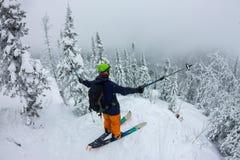 Man splitboard freerider standing at top of ridge. Ski touring in mountains, winter freeride extreme sport stock photo