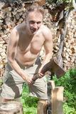 The man with a splitting axe prepares firewood Stock Photography