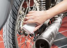 Man with sponge and cleaner soap clean up motorcycle. On the garage stock image
