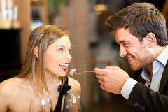 Man spoon-feeding his girlfriend Royalty Free Stock Photography