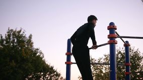 Man in sport clothes doing exercises on the horizontal bar outside in the sport ground in the park. Young man doing pull. Ups outside on nature stock video