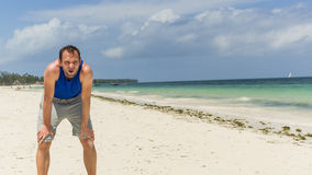 Man in sport clothing resting after exercise on beach. Royalty Free Stock Photos
