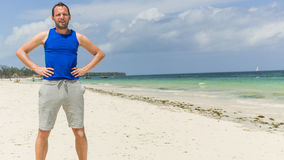 Man in sport clothing resting after exercise on beach. Stock Image