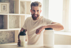 Man with sport nutrition. Handsome young bearded sportsman is looking at camera and smiling while preparing sport nutrition in kitchen at home Royalty Free Stock Photography