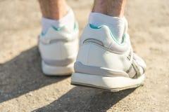 A man in sport sneakers walking on asphalt. A man in white sport sneakers walking on asphalt Royalty Free Stock Image