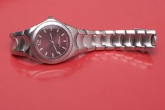 Man sport watch reflecting. Man sport watch on it's side, reflecting on red surface Royalty Free Stock Photos