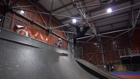 A man on roller skates trying to make jumps on the ramp and falls, slow motion. A man in sports clothes rolls on roller skates and falls in a skate park stock footage