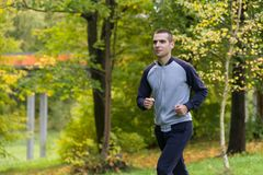 A man in sports clothes is running around stock photos