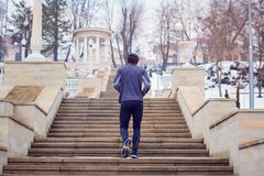 Man in sports clothes running up  stairs the park. Royalty Free Stock Photo