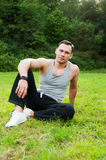 Man in sports clothes sitting on the grass in the Park Royalty Free Stock Photography
