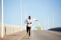 A man in a sports jacket runs in the early morning Royalty Free Stock Images