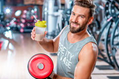 Man with sports nutrition. Muscular man drinking sports nutrition sitting with dumbbell in the gym Stock Image