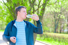 Man in a sports suit drinking water Stock Photography