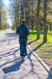 Man in a sports suit running in city park Royalty Free Stock Photo