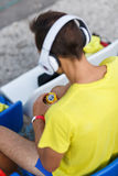 Man in sports uniform and headphones look at his watch sitting on a stadium seats after training Stock Photo