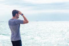 Man in sports wear looking at the sea outdoors Royalty Free Stock Image