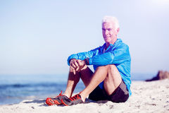 Man in sports wear sitting at the beach Stock Images