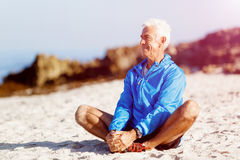 Man in sports wear sitting at the beach Royalty Free Stock Images