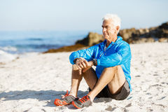 Man in sports wear sitting at the beach Stock Photos